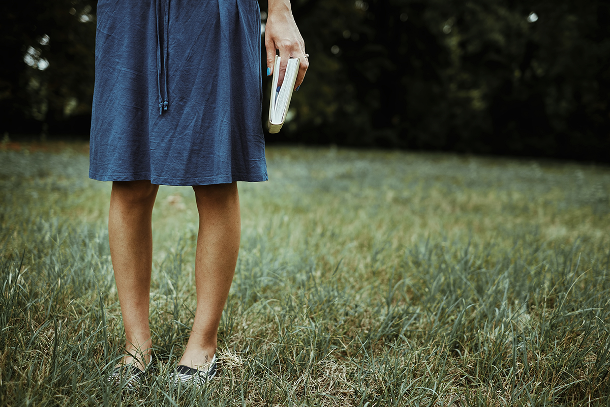 Woman holding her journal in a field